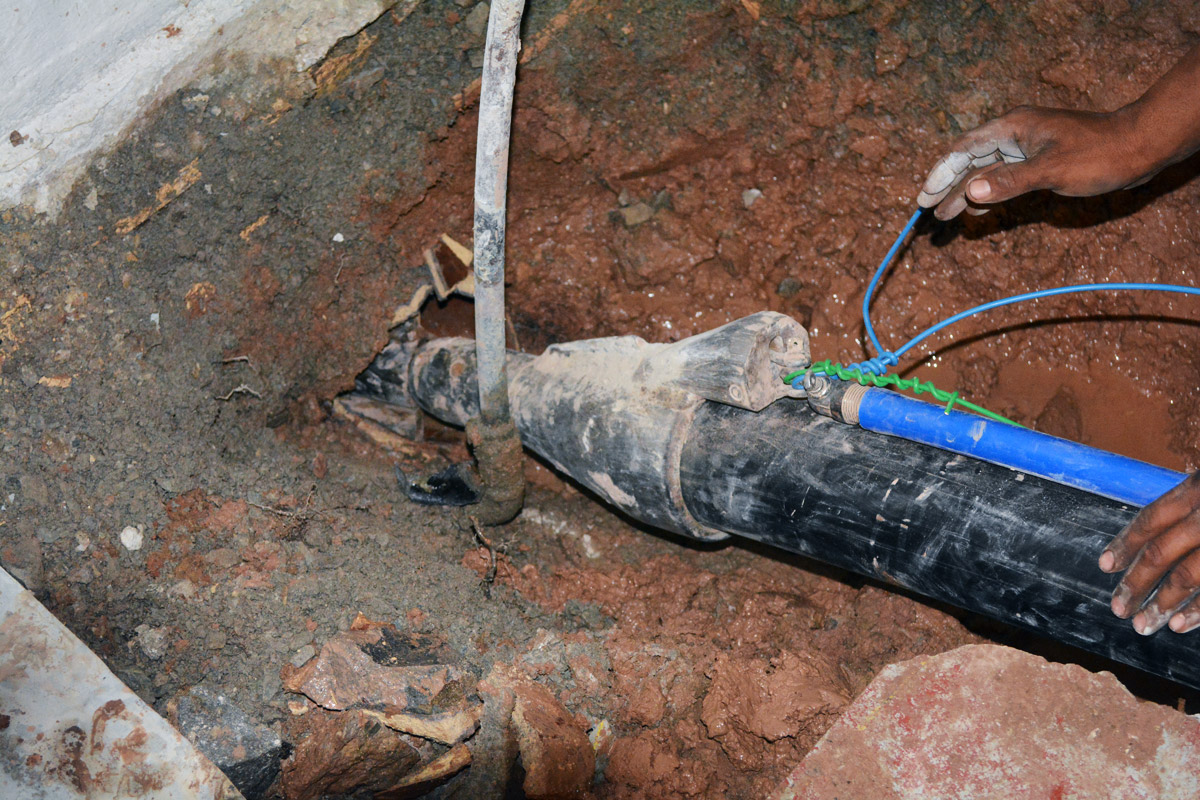 Pipe Bursting Head with new sewer and water lines attached entering under the house
